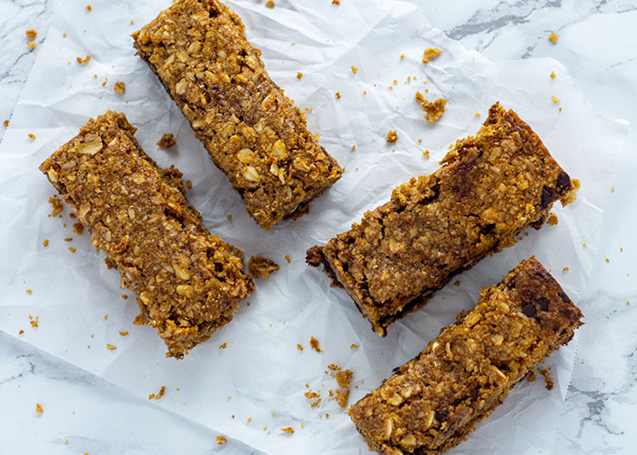 Four granola bars on a piece of wax paper on a white and grey marble surface