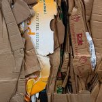 Pile of flattened cardboard boxes for recycling (with title overlay)