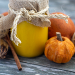 Pumpkin puree in a decorated mason jar next to fall decorations on a wooden surface (vertical with title overlay)