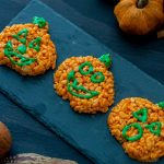 Pumpkin-shaped rice krispies with faces in green icing on a slate serving board on a dark wooden surface with fall decorations (vertical with title overlay)