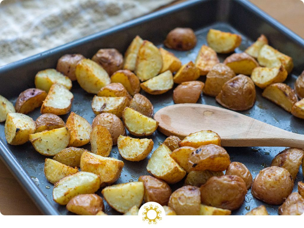 Roasted Potatoes with a wooden spoon on a metal baking sheet next to a tan towel on a light wooden surface (with logo overlay)