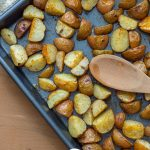 Roasted Potatoes with a wooden spoon on a metal baking sheet next to a tan towel on a light wooden surface (vertical with title overlay)