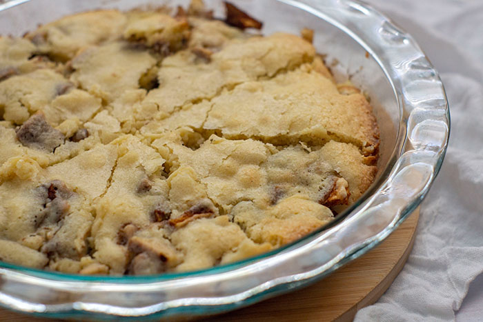 Baked easy apple pie in a glass pie pan on a circular bamboo platter on a white cloth surface