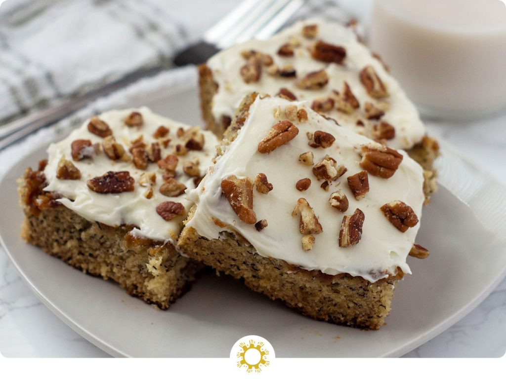 Three Banana Bread Bars topped with pecans on a square white plate with a stainless steel fork, glass of milk, and a white and grey towel behind the plate all on a white and grey marble surface (with logo overlay)