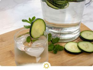 Cucumber Mint Infused Water in a glass with a pitcher behind it (with logo overlay)