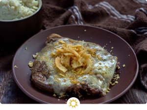 French Onion steak on a round brown plate with a brown towel and bowl of mashed potatoes behind all on a wooden surface (with logo overlay)