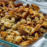 Baked homemade stuffing in a glass baking dish on top of a white and brown towel all on a white surface