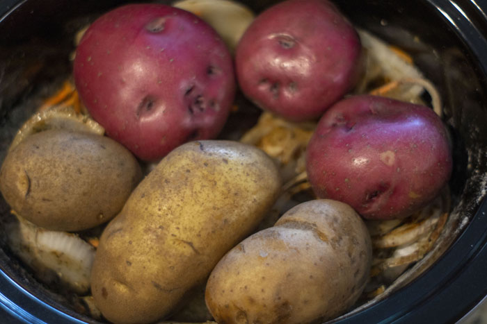 Close up of two types of potatoes placed on top of the mixed ingredients in the slow cooker
