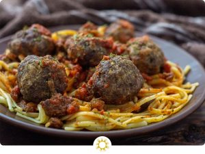 Spaghetti and Homemade Meatballs on a round brown plate next to a brown towel on a wooden surface (with logo overlay)