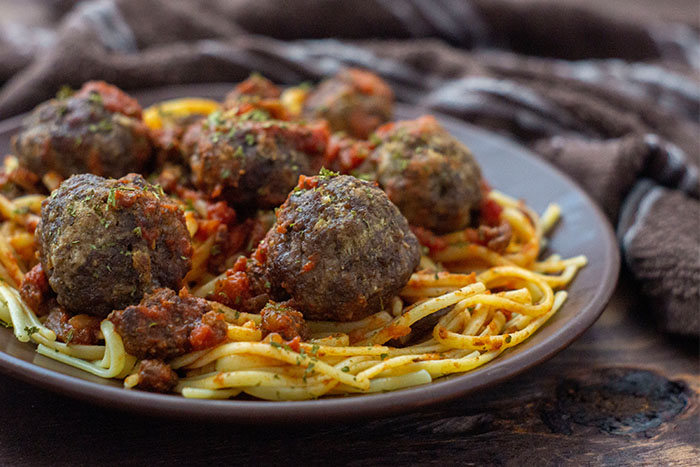 Spaghetti and Homemade Meatballs on a round brown plate next to a brown towel on a wooden surface