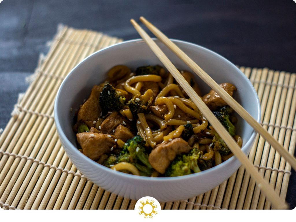 Teriyaki chicken with broccoli and udon noodles garnished with sesame seeds in a round white bowl with bamboo chopsticks on a bamboo mat on a wooden surface (with logo overlay)