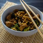 Teriyaki chicken with broccoli and udon noodles garnished with sesame seeds in a round white bowl with bamboo chopsticks on a bamboo mat on a wooden surface (vertical with title overlay)
