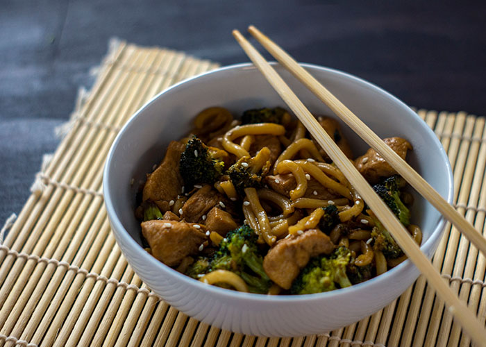 Teriyaki chicken with broccoli and udon noodles garnished with sesame seeds in a round white bowl with bamboo chopsticks on a bamboo mat on a wooden surface