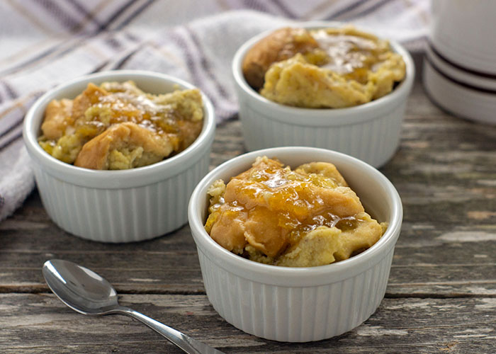 Three white ramekins filled with cooked bread pudding topped with whiskey sauce with a stainless steel spoon in front and a white and brown towel behind all on a wooden surface
