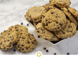 Chocolate chip cookies piled in a square white bowl with three cookies and a few chocolate chips to the side all on a white and grey marble surface (with logo overlay)