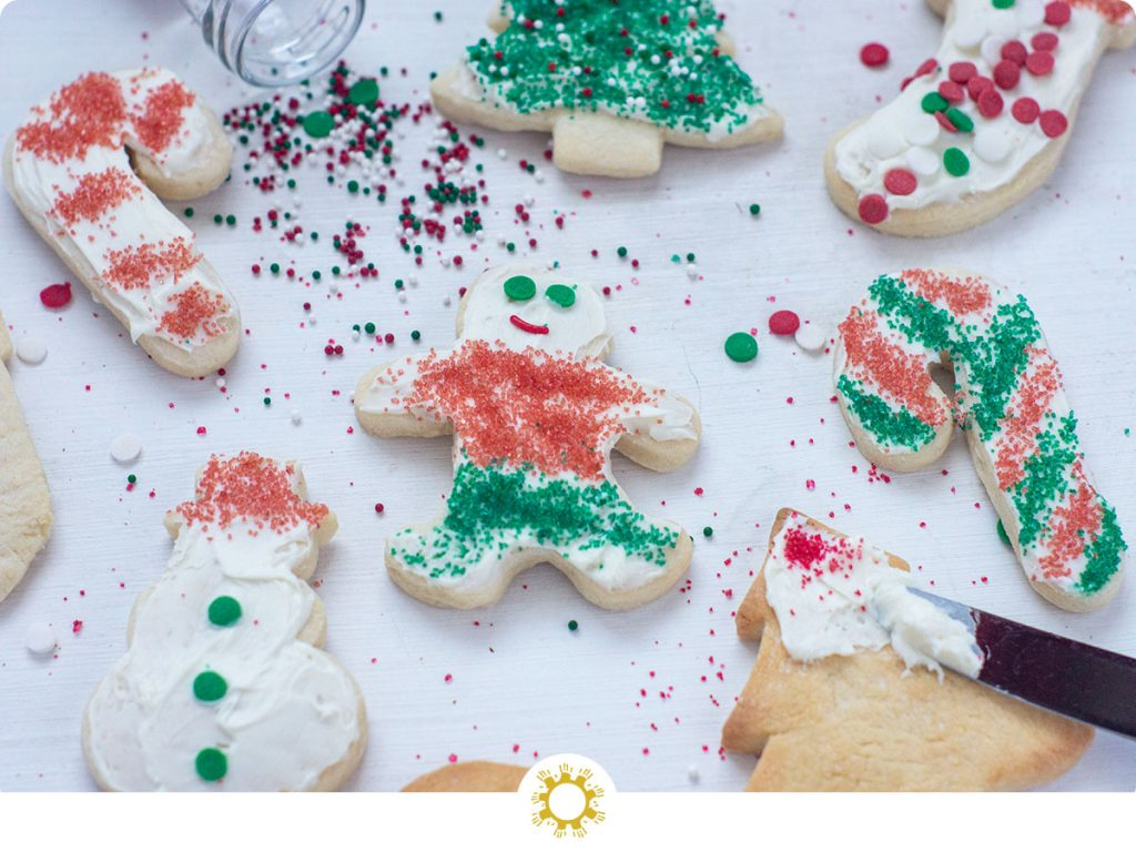 Christmas sugar cookies on a white surface with some frosted and decorated and a few unfrosted with spilled sprinkles (with logo overlay)