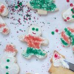 Christmas sugar cookies on a white surface with some frosted and decorated and a few unfrosted with spilled sprinkles (vertical with title overlay)