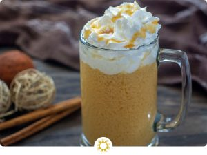 Glass mug of spiked hot apple cider topped with whipped cream and caramel sauce with fall decorations behind all on a wooden surface (with logo overlay)