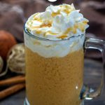Glass mug of spiked hot apple cider topped with whipped cream and caramel sauce with fall decorations behind all on a wooden surface (vertical with title overlay)