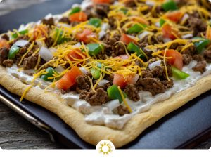 Baked taco pizza on a baking stone on a wooden surface (with logo overlay)