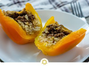 Orange bell peppers stuffed with rice and ground beef cut in half sitting on a white round plate with a white and brown towel behind (with logo overlay)