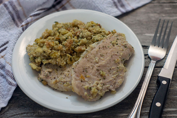 Un-stuffed Pork Chops on a round white plate with a white and grey towel behind and a fork in front on a wooden surface