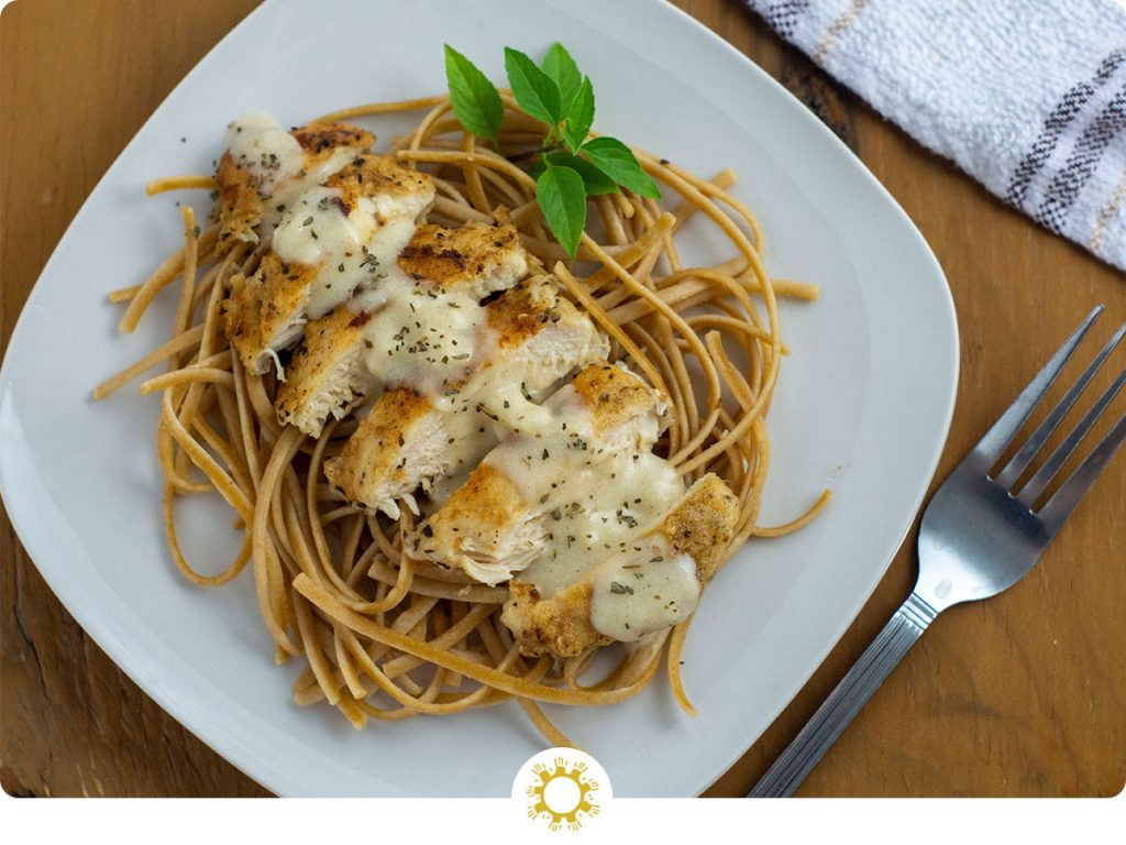 White Cheddar Chicken Pasta garnished with a sprig of basil on a square white plate next to a stainless steel fork with a white and brown towel behind all on a wooden surface (with logo overlay)