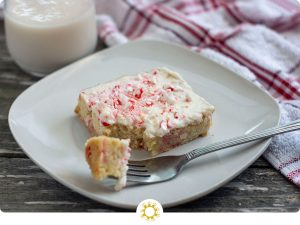 White Chocolate Blondie with Peppermint frosting on a square white plate with a bit on a fork in front of a white and red towel and a glass of milk all on a wooden surface (with logo overlay)