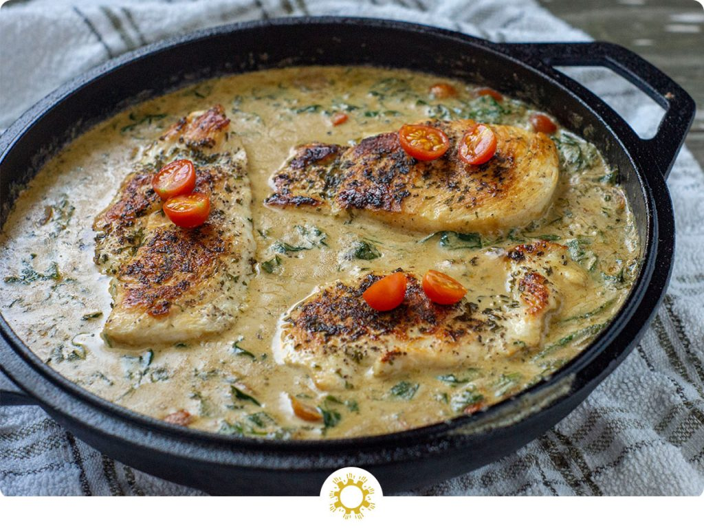 Cooked chicken breasts topped with sliced tomatoes sitting in a cream sauce in a cast iron pan on a white and brown towel (with logo overlay)