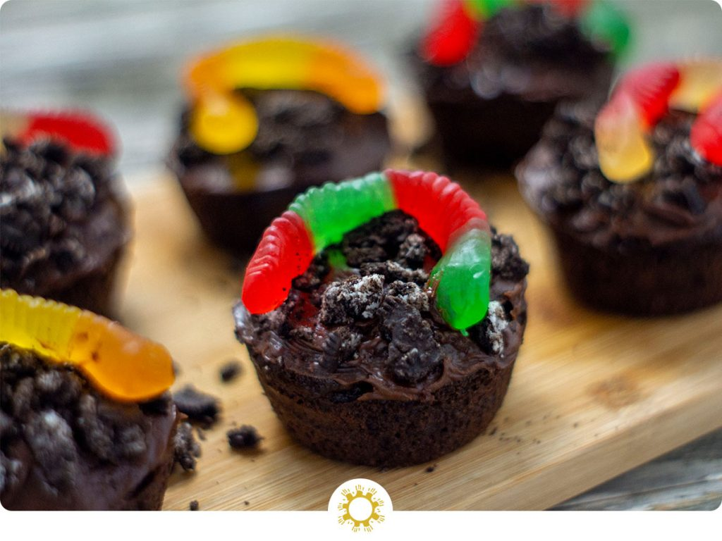 Dirt cupcakes covered with crushed oreos and topped with a gummy worm on a bamboo platter on a wooden surface (with logo overlay)