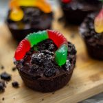 Dirt cupcakes covered with crushed oreos and topped with a gummy worm on a bamboo platter on a wooden surface (vertical with title overlay)