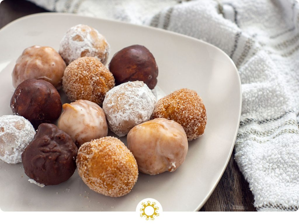 Variety of homemade doughnuts on a rounded square white plate next to a white towel on a wooden surface (with logo overlay)
