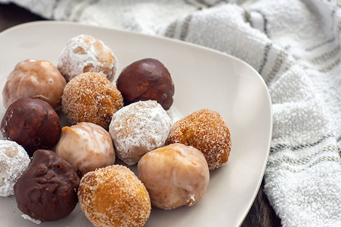 Variety of homemade doughnuts on a rounded square white plate next to a white towel on a wooden surface