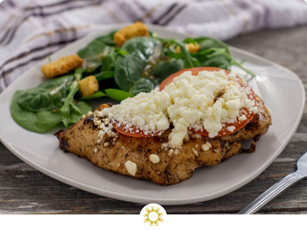 Feta-topped chicken on a square white plate next to a salad with a fork in front and a white and brown towel behind all on a wooden surface (with logo overlay)