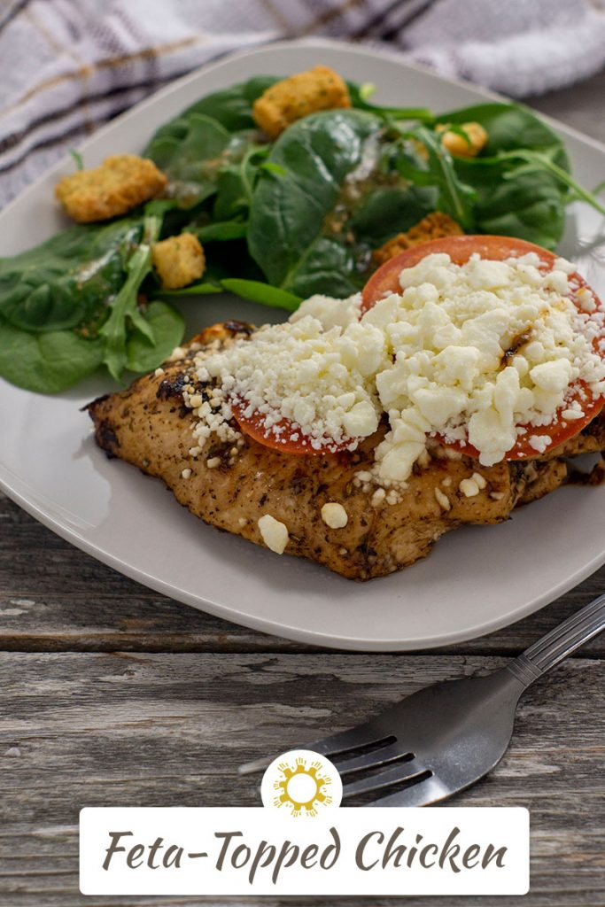 Feta-topped chicken on a square white plate next to a salad with a fork in front and a white and brown towel behind all on a wooden surface (vertical with title overlay)