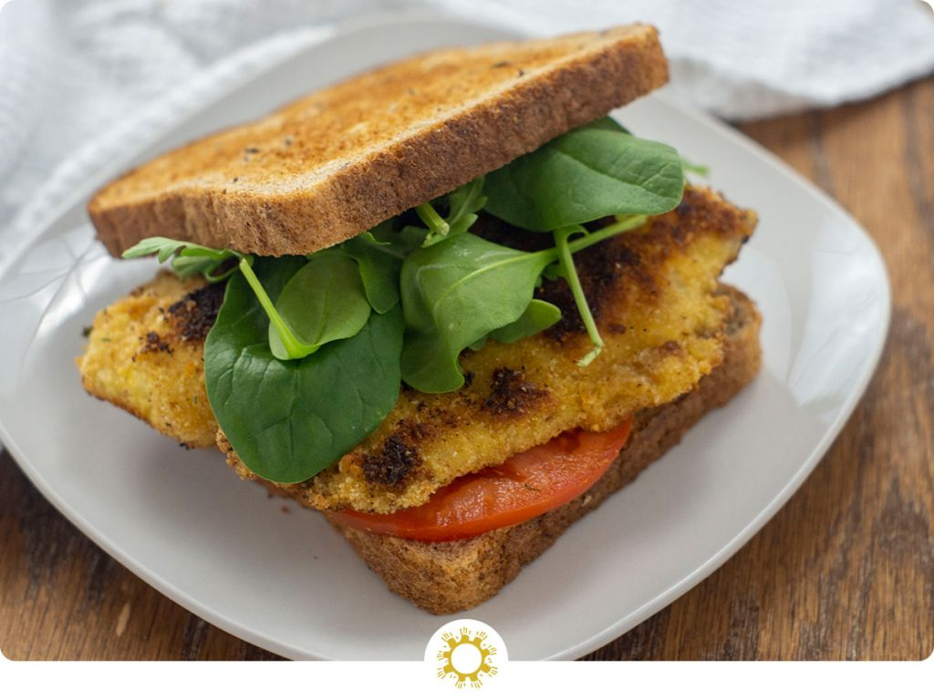 Fried tilapia sandwich wiht sliced tomato and fresh spinach on a square white plate with a white towel behind on a wooden surface (with logo overlay)