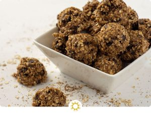 Oatmeal Energy Balls in a square bowl with a few next to the bowl on a white surface sprinkled with oats, flax seed, and chia seeds (with logo overlay)
