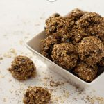 Oatmeal Energy Balls in a square bowl with a few next to the bowl on a white surface sprinkled with oats, flax seed, and chia seeds (vertical with title overlay)
