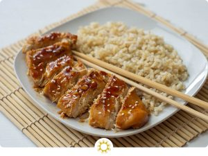 Orange chicken on a white plate with brown rice and chopsticks (with logo overlay)