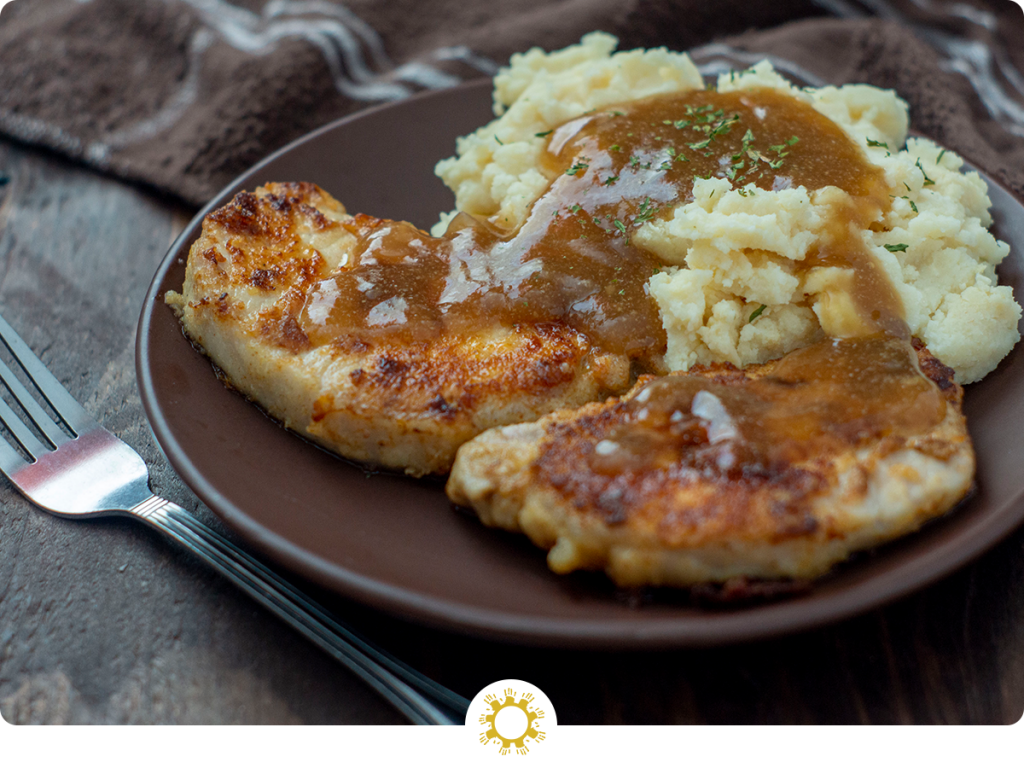 Pan-Fried Pork Chops with Brown Gravy next to mashed potatoes covered with gravy on a round brown plate next to a fork with a brown towel in the background all on a wooden surface (with logo overlay)