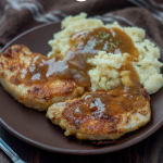 Pan-Fried Pork Chops with Brown Gravy next to mashed potatoes covered with gravy on a round brown plate next to a fork with a brown towel in the background all on a wooden surface (vertical with title overlay)