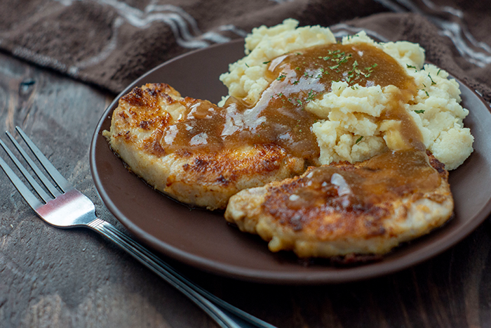 Pan-Fried Pork Chops with Brown Gravy next to mashed potatoes covered with gravy on a round brown plate next to a fork with a brown towel in the background all on a wooden surface