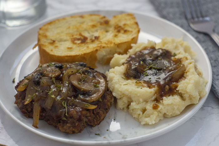 Salisbury Steak with mashed potatoes covered with salisbury gravy and a piece of garlic toast on a round white plate with a grey napkin and fork behind all on a white and grey marble surface