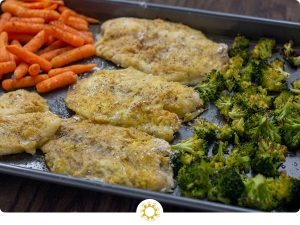 Breaded baked tilapia in the center of roasted broccoli and carrots on a metal sheet pan on a wooden surface (with logo overlay)