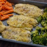 Breaded baked tilapia in the center of roasted broccoli and carrots on a metal sheet pan on a wooden surface