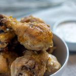 Southern fried chicken drumsticks in a round white bowl next to a smaller round white bowl with gravy on a grey placemat on a wooden surface (vertical with title overlay)