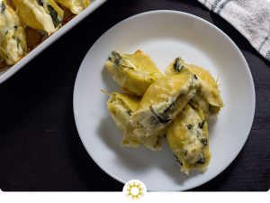 Five spinach and artichoke stuffed shells piled on a round white plate next to a white casserole dish with more shells and a white and blue towel behind all on a wooden surface (with logo overlay)