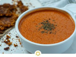 Tomato soup with a garnish of parsley in a white bowl next to parmesan crisp crumbles on a white surface (with logo overlay)