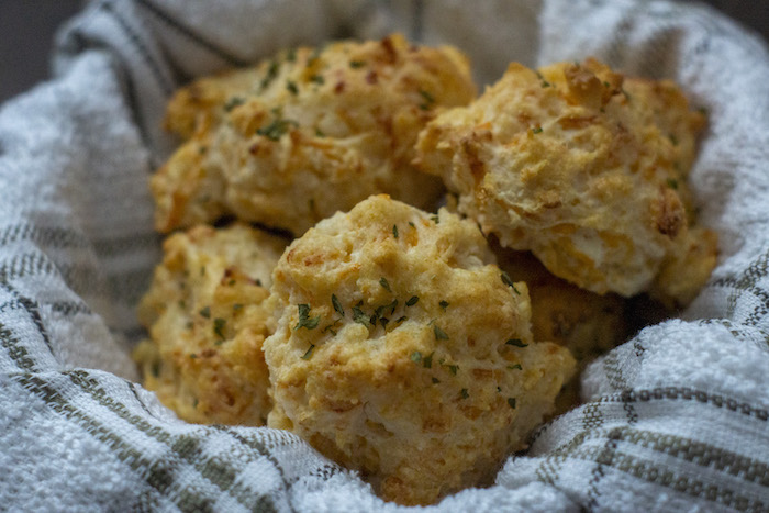 Cheddar Biscuits in a basket covered with a towel