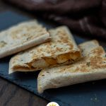 3 pieces of chicken and cheese quesadillas on a slate tray with a brown and white towel behind all on a wooden surface (vertical with title overlay)
